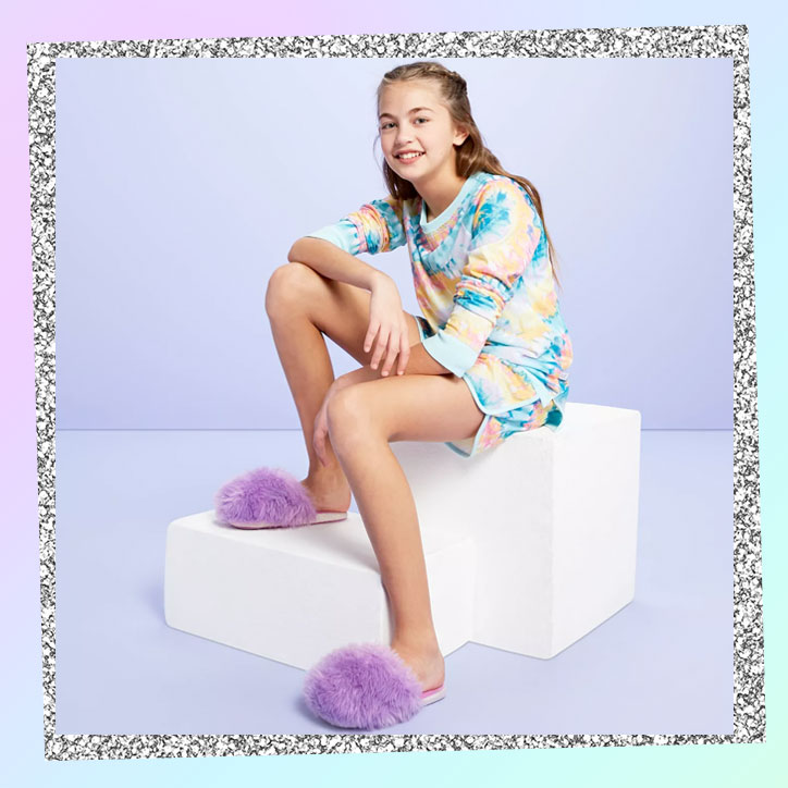 Tween girl wearing a pastel tie-dye pajama set at fluffy purple slippers