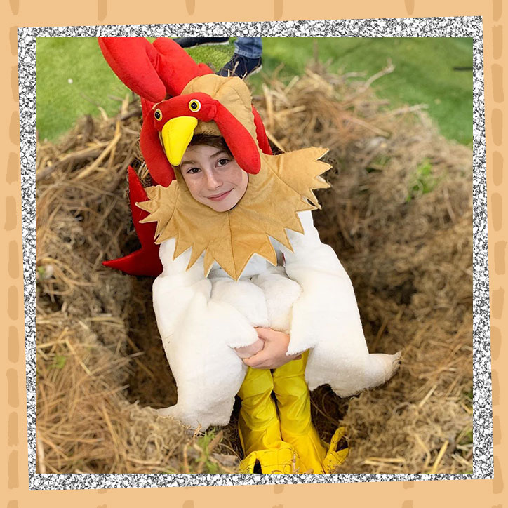 Actor Paxton Booth wearing a chicken suit while sitting in a nest