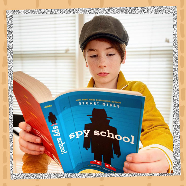 Actor Paxton Booth reading a copy of Spy School by Stuart Gibbs