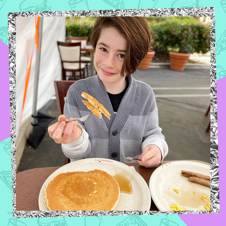 Actor Paxton Booth eating a plate of pancakes
