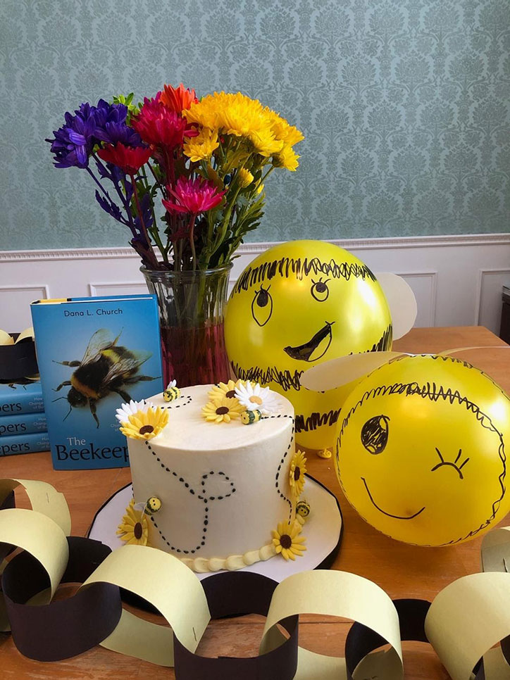 Bee balloons, a vase of flowers, a bee cake, and garland sitting on a table