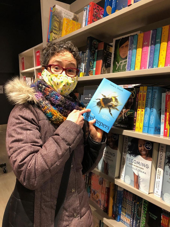 Author Dana L. Church holding a copy of The Beekeepers in a library