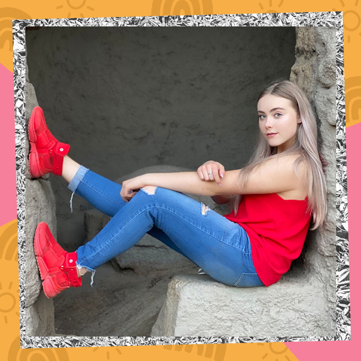 Mila Nabours sits on a stone bench with her legs up on a stone wall