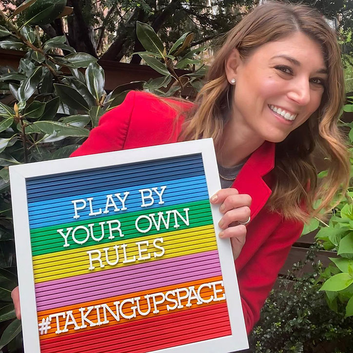 """Author Alyson Gerber wears a red pantsuit and holds up a rainbow sign stating """"Play By Your Own Rules #TakingUpSpace"""""""