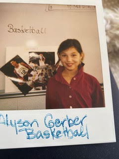 Author Alyson Gerber as a kid, standing in front of her elementary school report about basketball