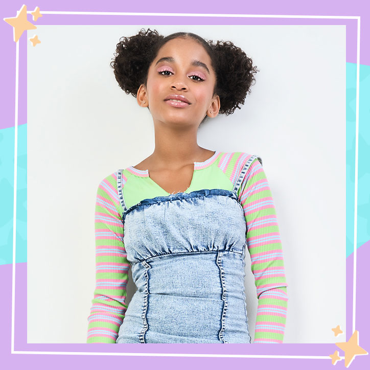 Actress Jordyn Curet poses against a blank wall, wearing a colorful striped shirt, denim dress, and her hair up in space buns