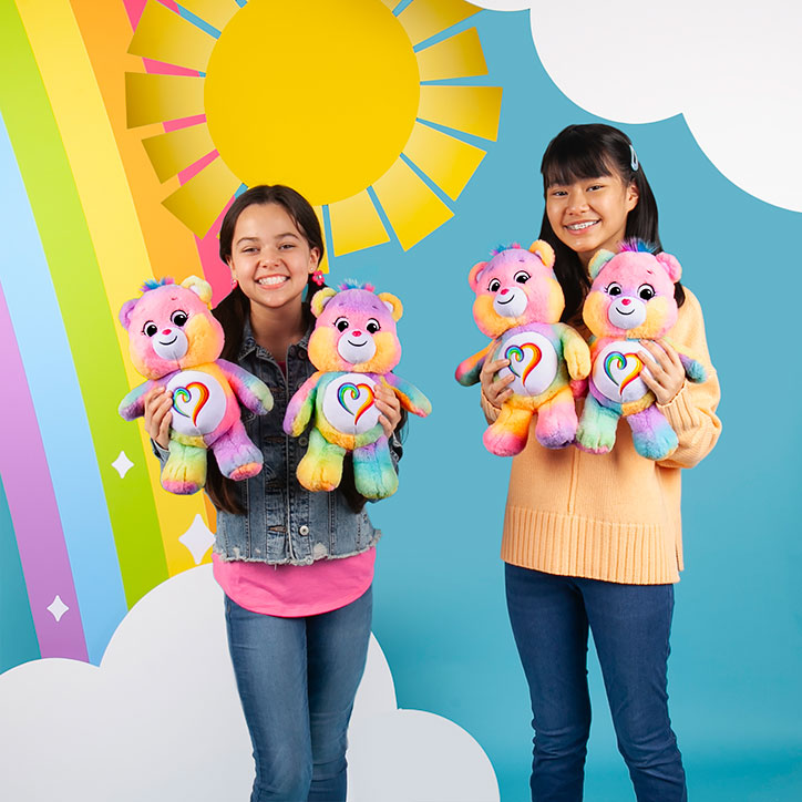 Two tween girls standing in front of a rainbow backdrop holding up Togetherness Bear Care Bears plush toys