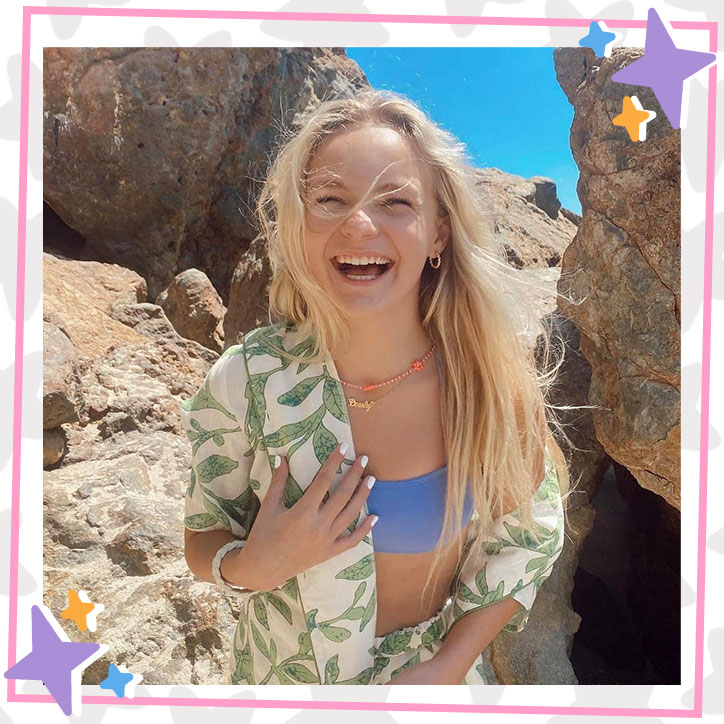 Pressley Hosbach laughs on the beach in a floral overshirt, shorts, and a blue bathing suit top