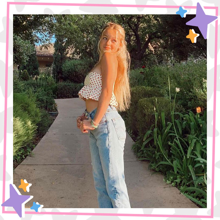Pressley Hosbach poses with her hair pulled back in a polkadot crop top and jeans