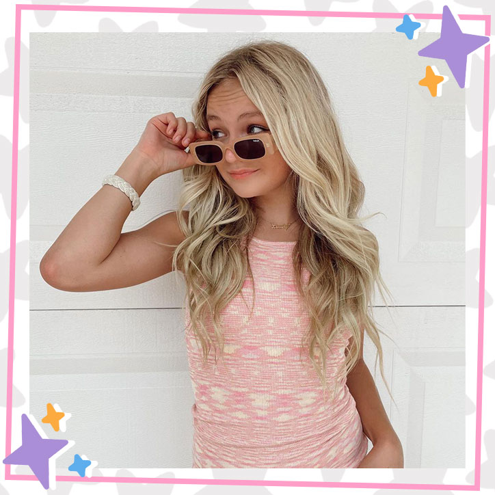 Pressley Hosbach poses in front of a wall in a pink dress, tipping her sunglasses