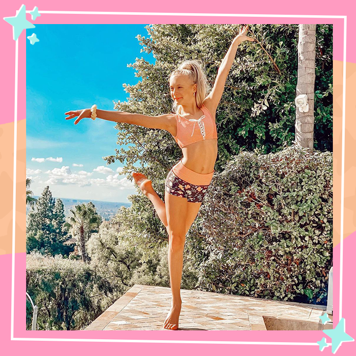 Dancer Katie Couch poses with her arms in the air, balanced on one leg