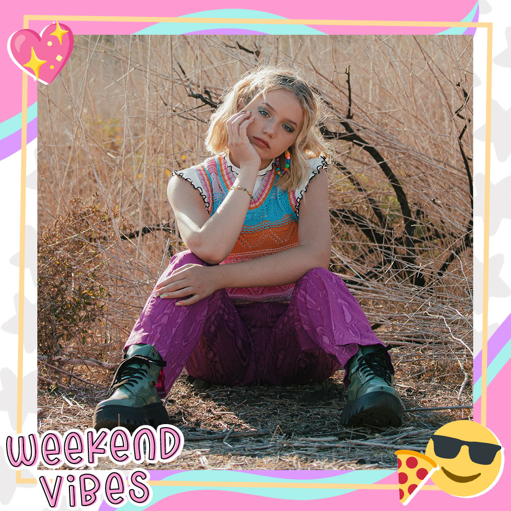 Indi Star sits in the desert with her hand on her chin while wearing a colorful outfit