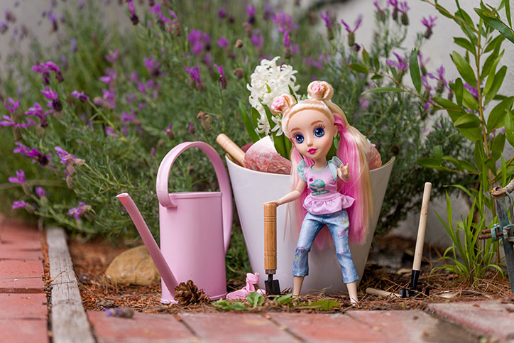 Brianna of the B-Kind Dolls standing in a garden next to a pink watering can and bucket of gardening tools.
