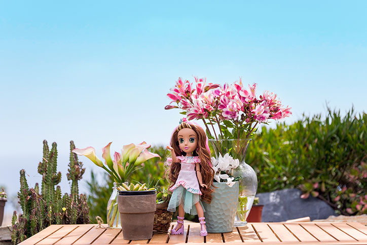Ivy from the B-Kind Dolls poses in front of a desert backdrop and pretty plants