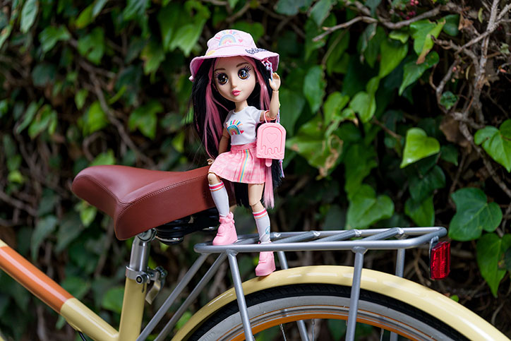 Nora from the B-Kind Dolls sits on the rack of a bicycle