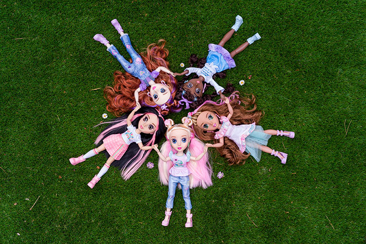 All five B-Kind dolls laying in the grass in a circle while holding hands