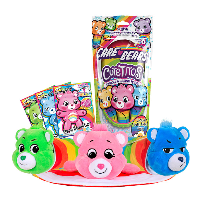 Care Bears Cutetitos Packaging with Cheer Bear, Grumpy Bear, and Good Luck bear laying in front on top of one of their belly badge wraps. Image also shows character cards for each of the three characters shown.