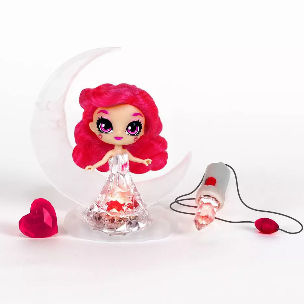 Rose Quartz Crystalina doll sitting on her crescent moon shaped base with a heart shaped hairclip and crystal amulet necklace