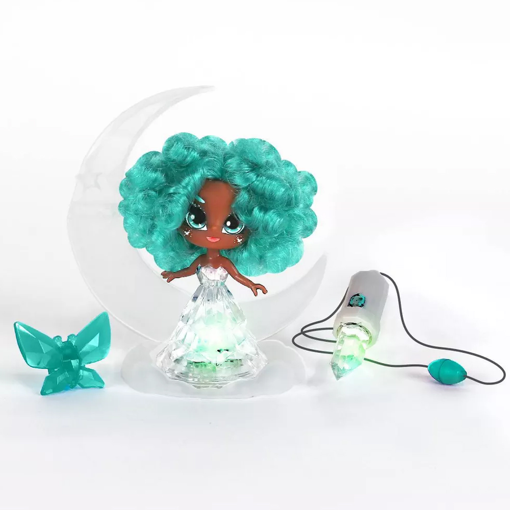 Turquoise Crystalina doll sitting on her crescent moon shaped base with a butterfly shaped hairclip and crystal amulet necklace