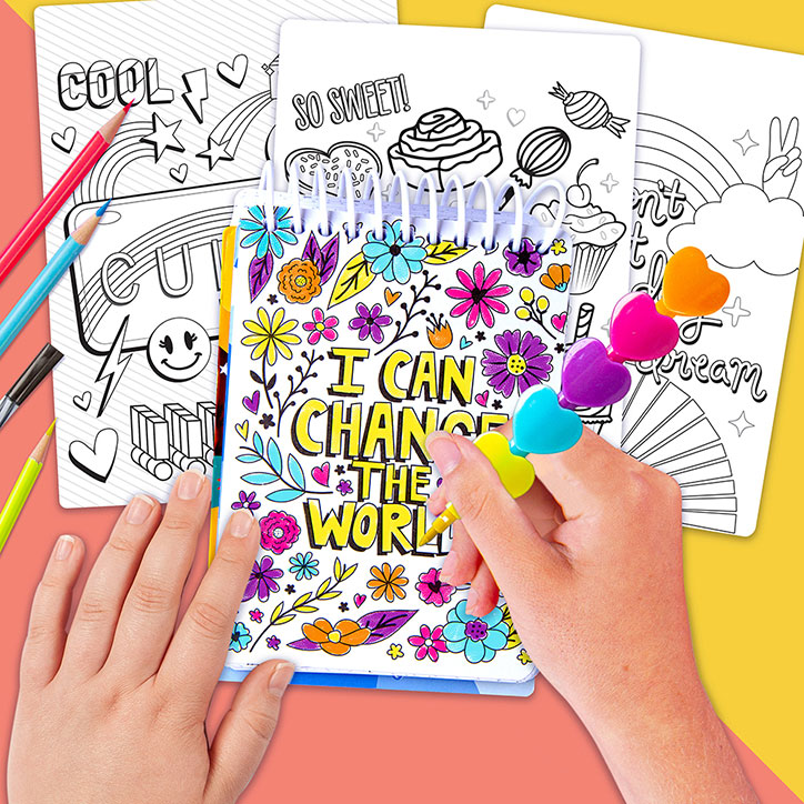 """Flat lay of a girl using the included heart shaped crayon, coloring a quote graphic that says """"I Can Change the World"""" from the Fashion Angels Positivity Doodles Activity Set"""