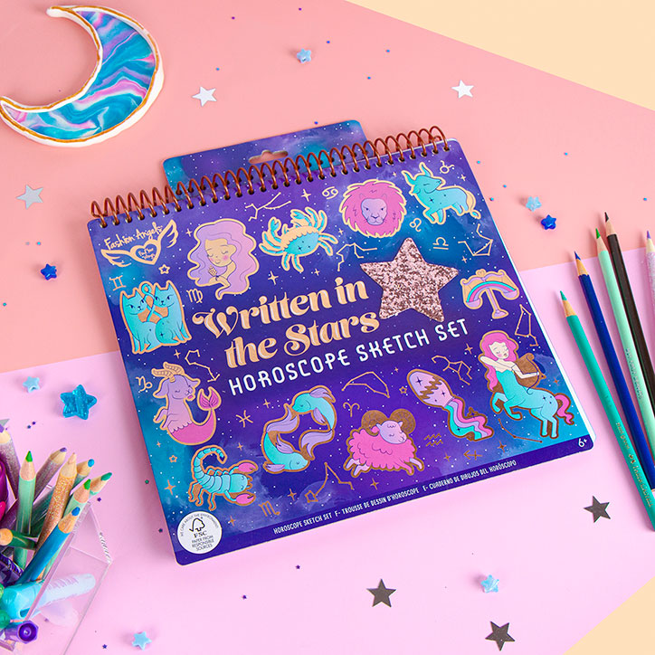 Flat Lay of the Written in the Stars Horoscope Sketch set laid out over pink and orange paper, with star confetti, pastel colored pencils, and star confetti