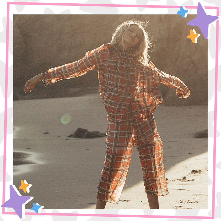 Indi Star poses on the beach in a flowy, burnt orange plaid pant suit