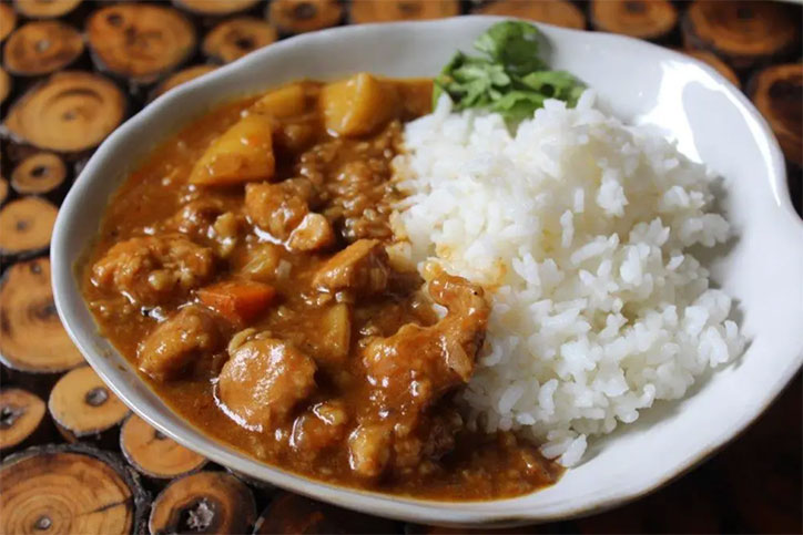 A bowl of Japanese curry with chicken, vegetables, and white rice