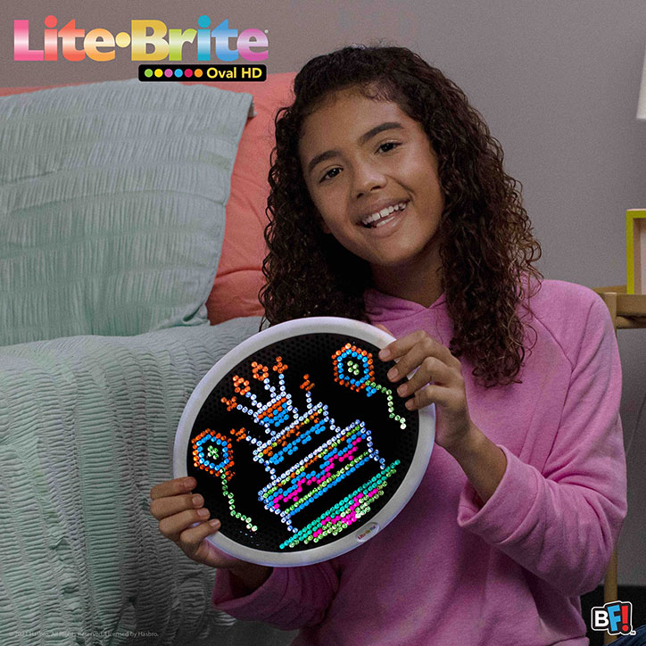 A tween girl holding up a design of a birthday cake and balloons she created on a Lite-Brite Oval HD