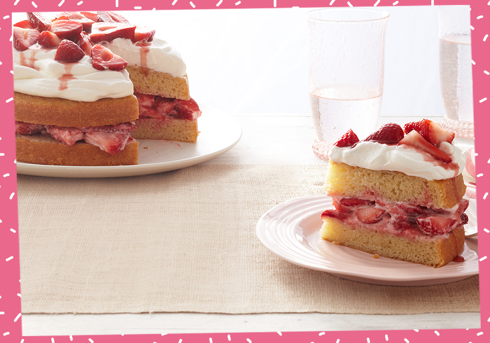 A strawberry shortcake layer cake sitting on top of a white plate on a tan placement, with a slice of the same cake off to the right on a similar plate.
