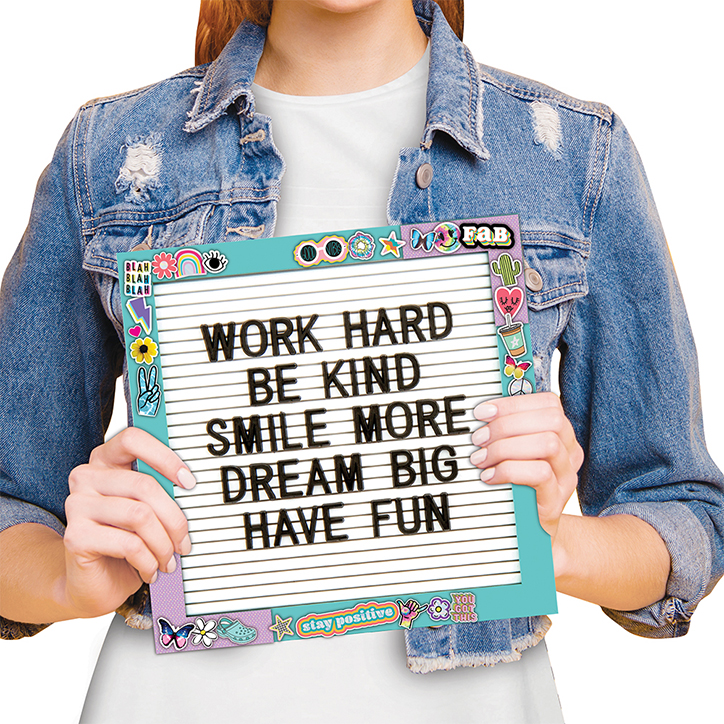 """Tween girl in a denim jacket holding up the letter board found in the Fashion Angels Letter Board Design Kit. Letter board is covered in stickers around the frame and the message says """"Work Hard, Be Kind, Smile More, Dream Big, Have Fun"""""""