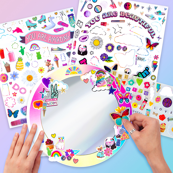Flat lay of the Fashion Angels Sticker Collage Mirror Design Kit including two sticker sheets and a rainbow framed mirror