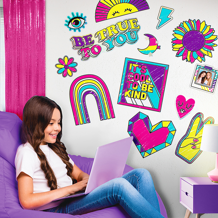 Tween girl sitting in a purple beanbag chair using a laptop in front of a wall filled with DIY decals from the Dream Gallery Wall kit from Fashion Angels