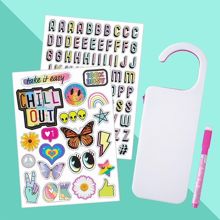 Flat lay of the Fashion Angels Light Up Door Hanger Kit including two sticker sheets, a dry erase marker, and the door hanger