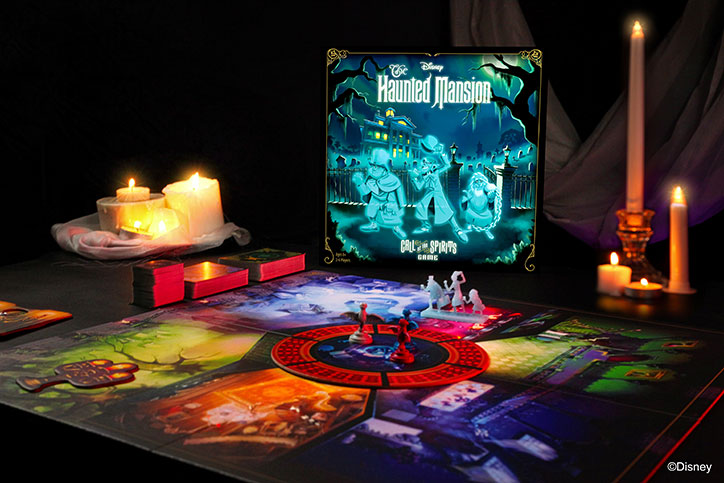 Product shot of the Disney Haunted Mansion: Call of the Spirits Game including box art, game board, and included pieces laid out on a table in a dim room with candles all around