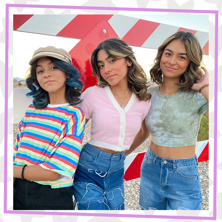 GEM Sisters Evangeline, Mercedes, and Giselle posing together in front of a construction zone