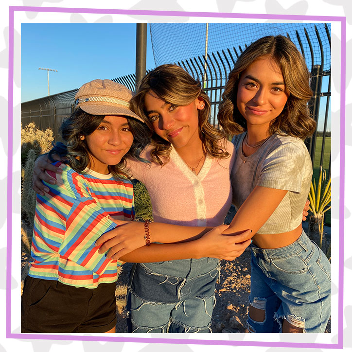 GEM Sisters Evangeline, Mercedes, and Giselle hugging outdoors as the sun sets in front of a fence
