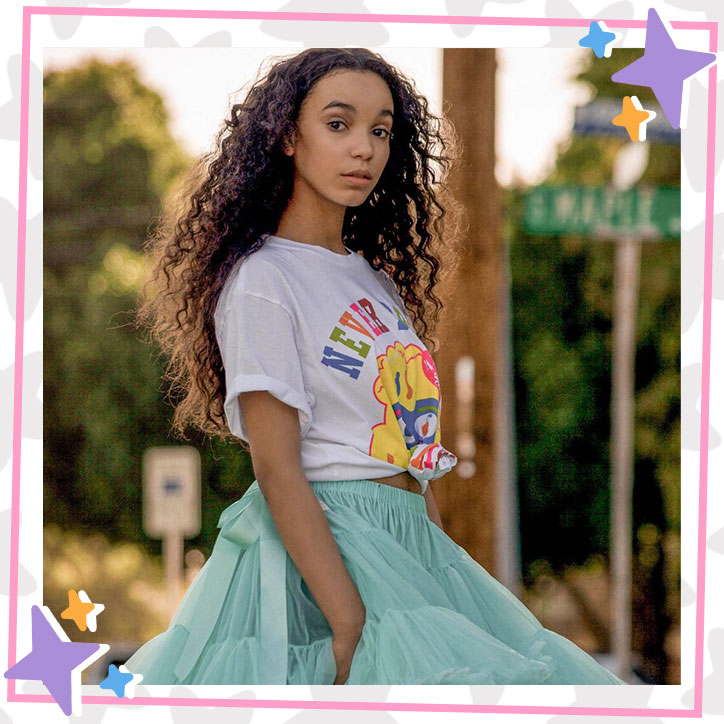 Kherrington Briggs poses outdoors in a baggy white t-shirt and fluffy teal tutu