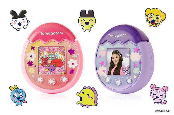 Two Tamagotchi Pix devices (Pink and Purple) side by side with Tamagotchi characters all around them