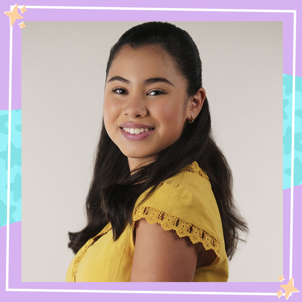 Tess Romero poses in a yellow top in character as Elena from Diary of a Future President