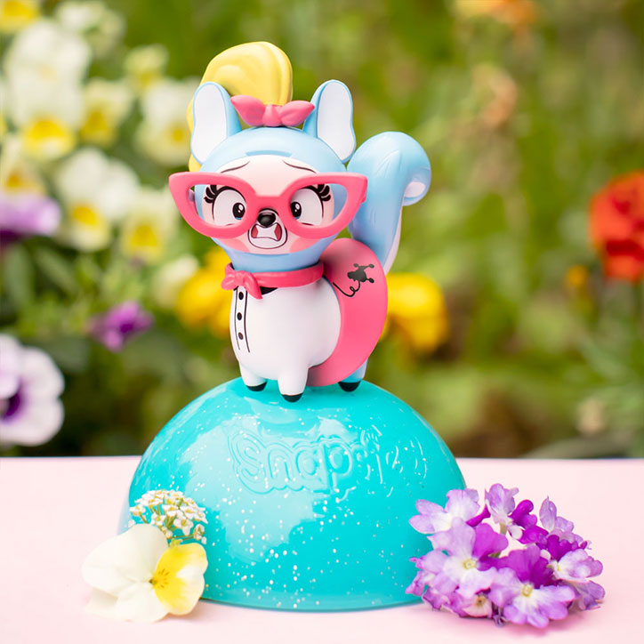 A Snapsies Series 2 figure posed on top of their capsule while wearing big pink glasses, a poodle skirt, and a big yellow ponytail