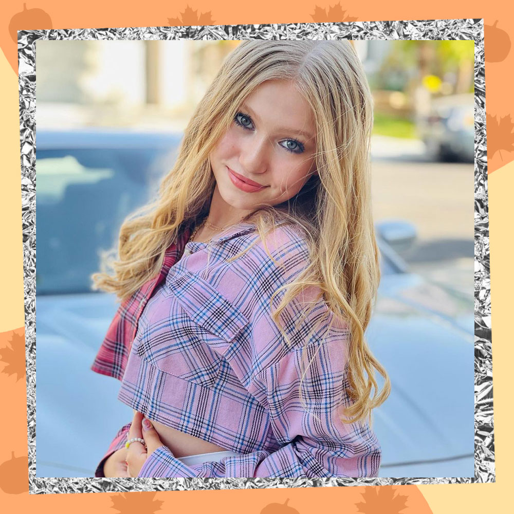Abigail Zoe Lewis poses in a cropped plaid baby pink jacket with her long blonde hair flowing over her shoulders