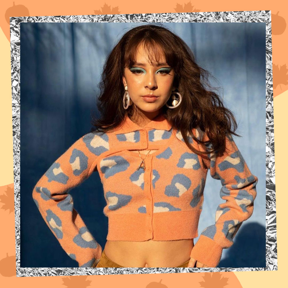 Aubrey Anderson-Emmons poses confidently in a pastel orange leopard print cropped cardigan, big hoop earrings, and bold green eyeshadow