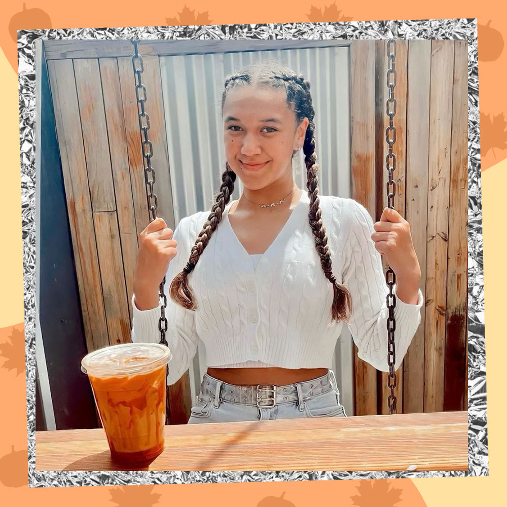 Keilahni Dixon poses on a swing in a cropped white cable-knit sweater and long braids. A pumpkin spice latte sits on the table in front of her.