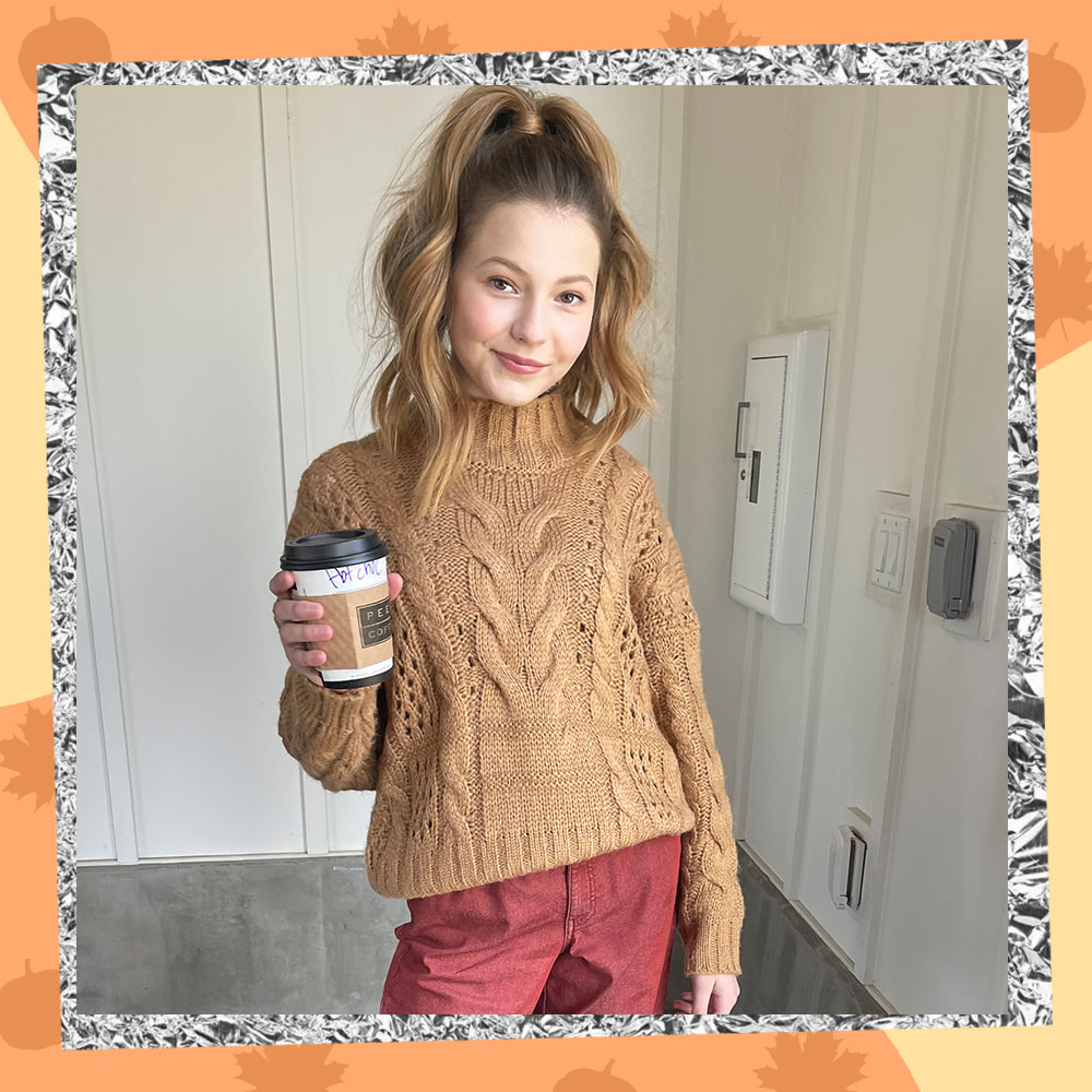 Lilo Baier poses in a tan cable knit sweater and salmon pants while holding a pumpkin spice latte