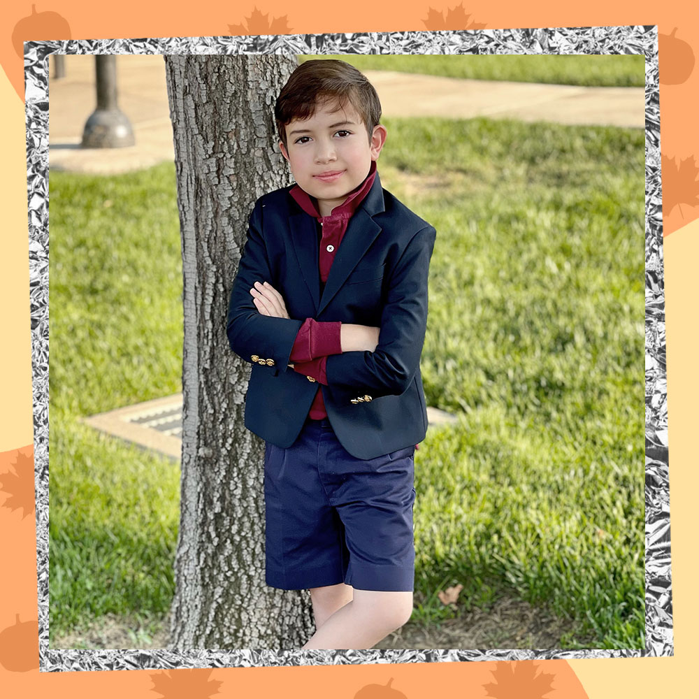 Miguel Gabriel poses in front of a tree wearing his school uniform
