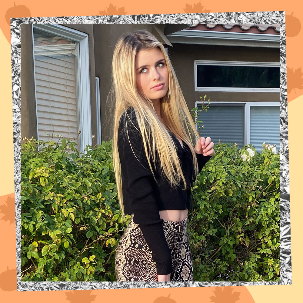 Ruby Lightfoot poses in front of her house with long blonde hair, a cropped black cardigan, and snake print leggings