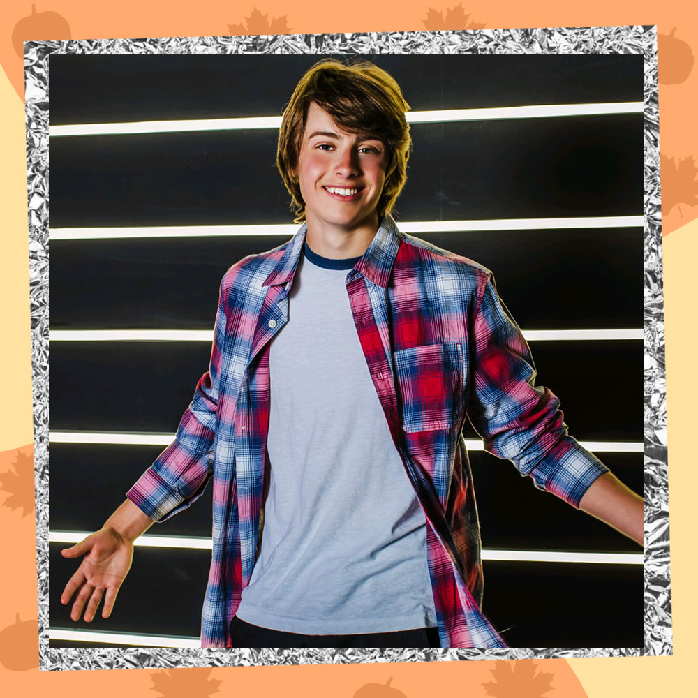 Ryker Baloun poses in front of a lit up wall in a red plaid flannel with his arms spread wide
