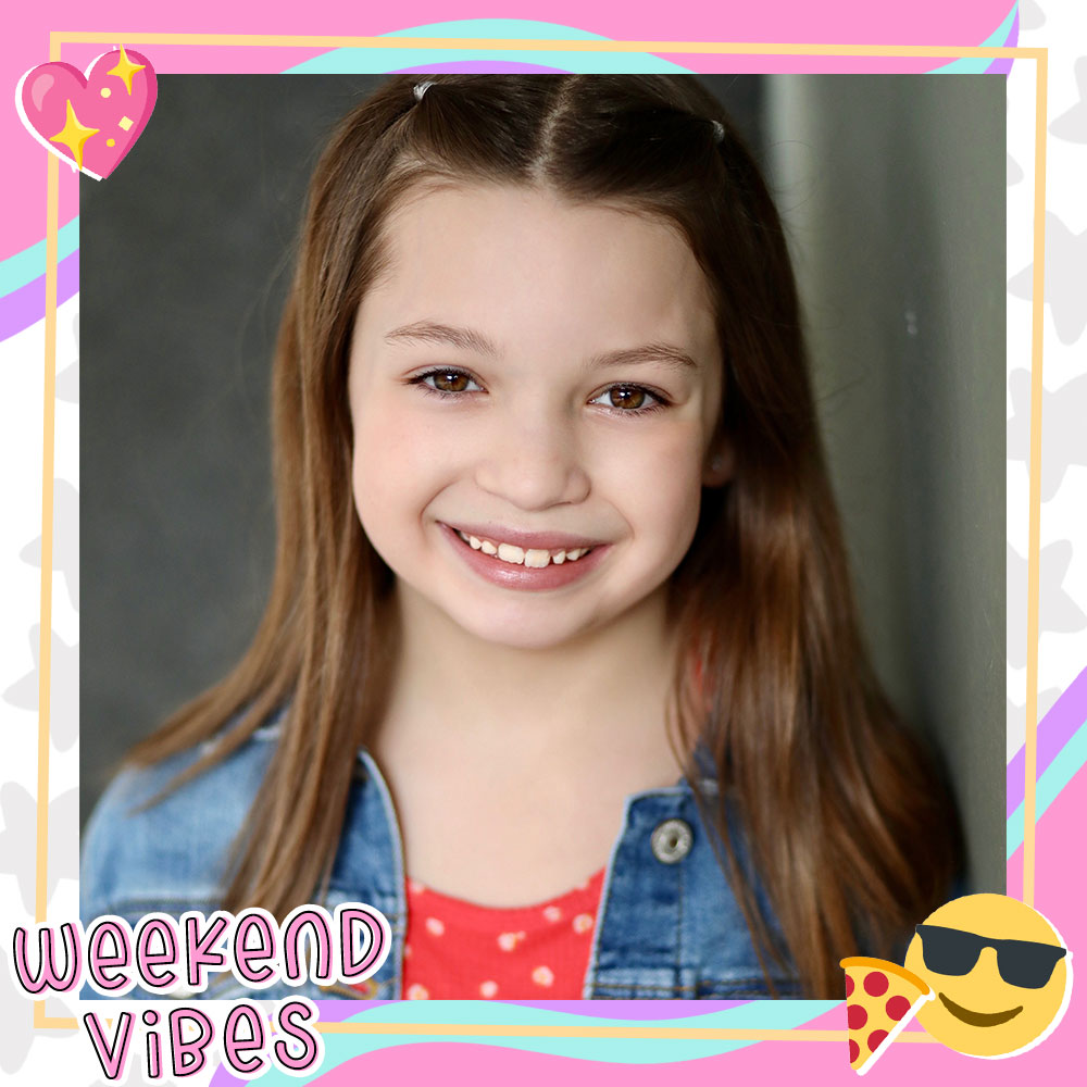 Closeup of Dalya Knapp smiling big, long brown hair in small pigtails, wearing a denim jacket over a red and white polkadot shirt